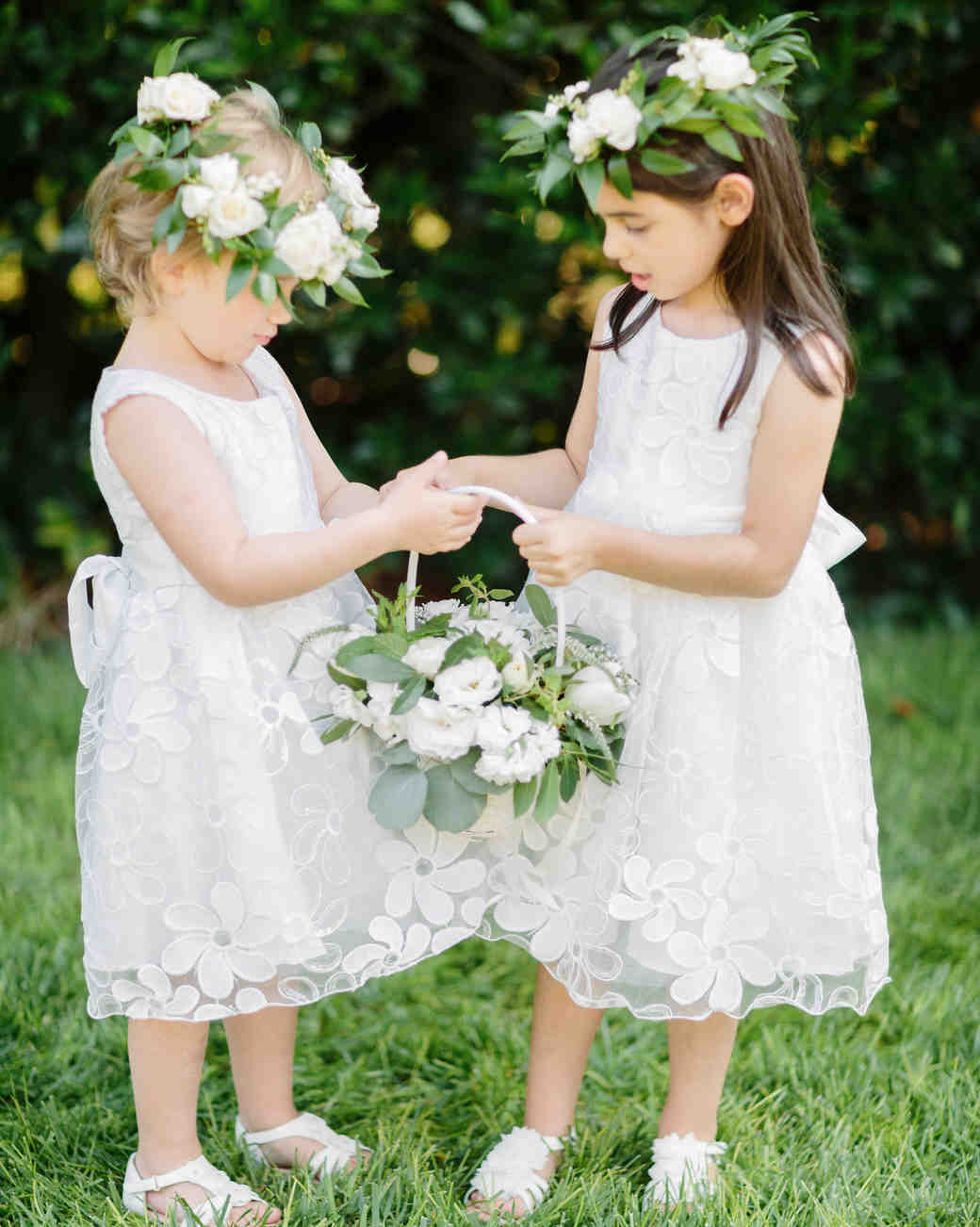two flower girls holding a white wicker basket