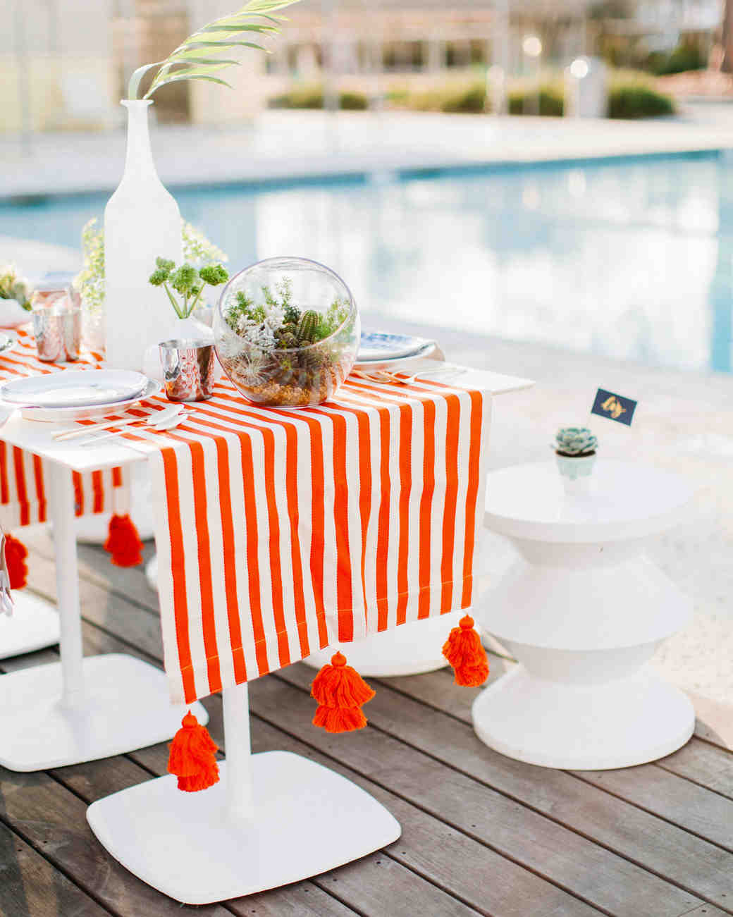striped bright red table runner with greenery by pool