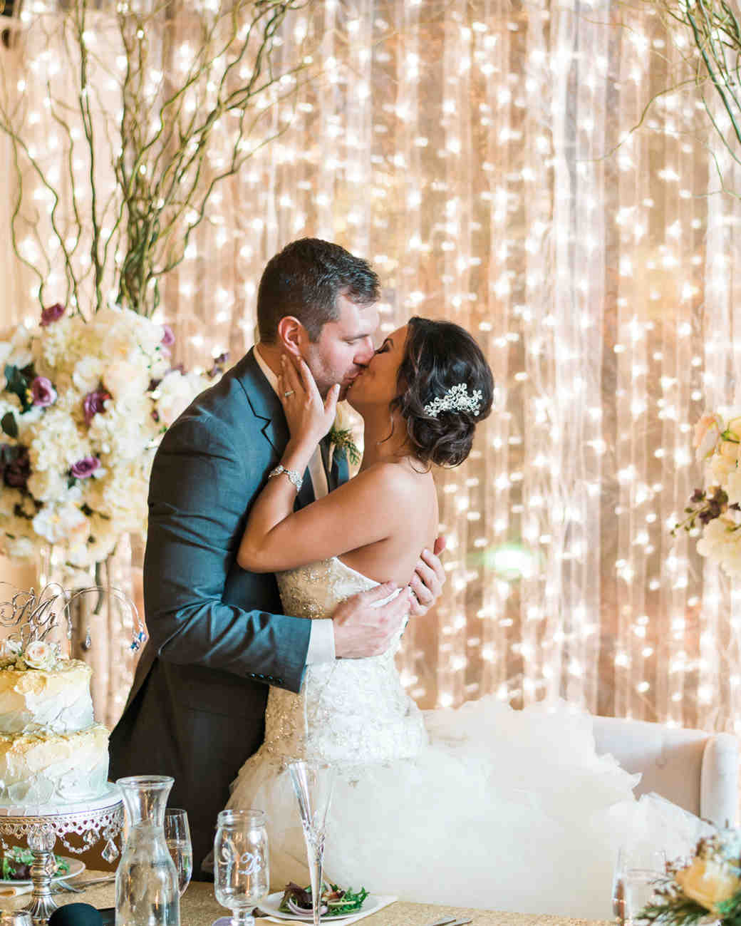 twinkle lights against reception wall with couple kissing