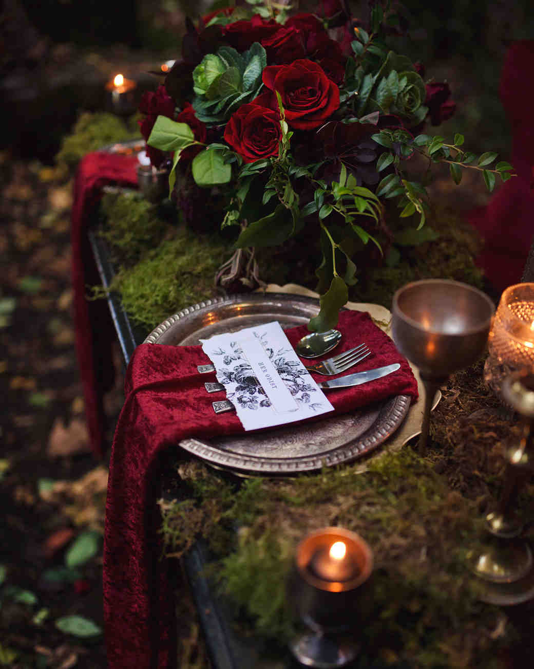 silver and red place setting with roses and moss