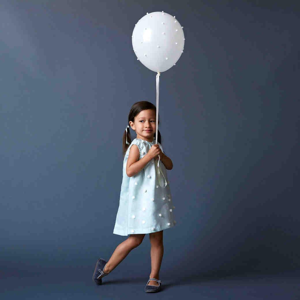 kid with pom pom balloon opener