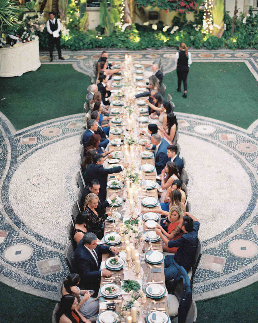 guests seated at family style long reception table outside