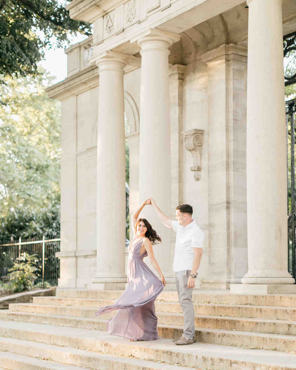 couple twirling on front steps engagement photo