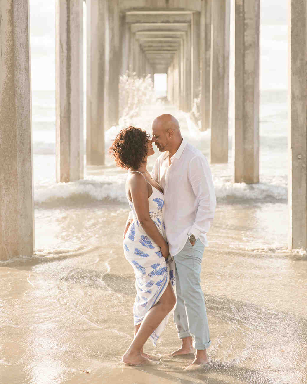 couple under beach boardwalk engagement photo