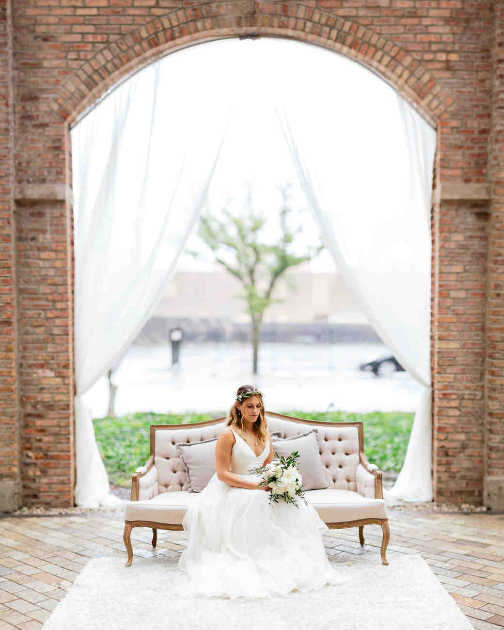 bride sitting on white couch below brick arch