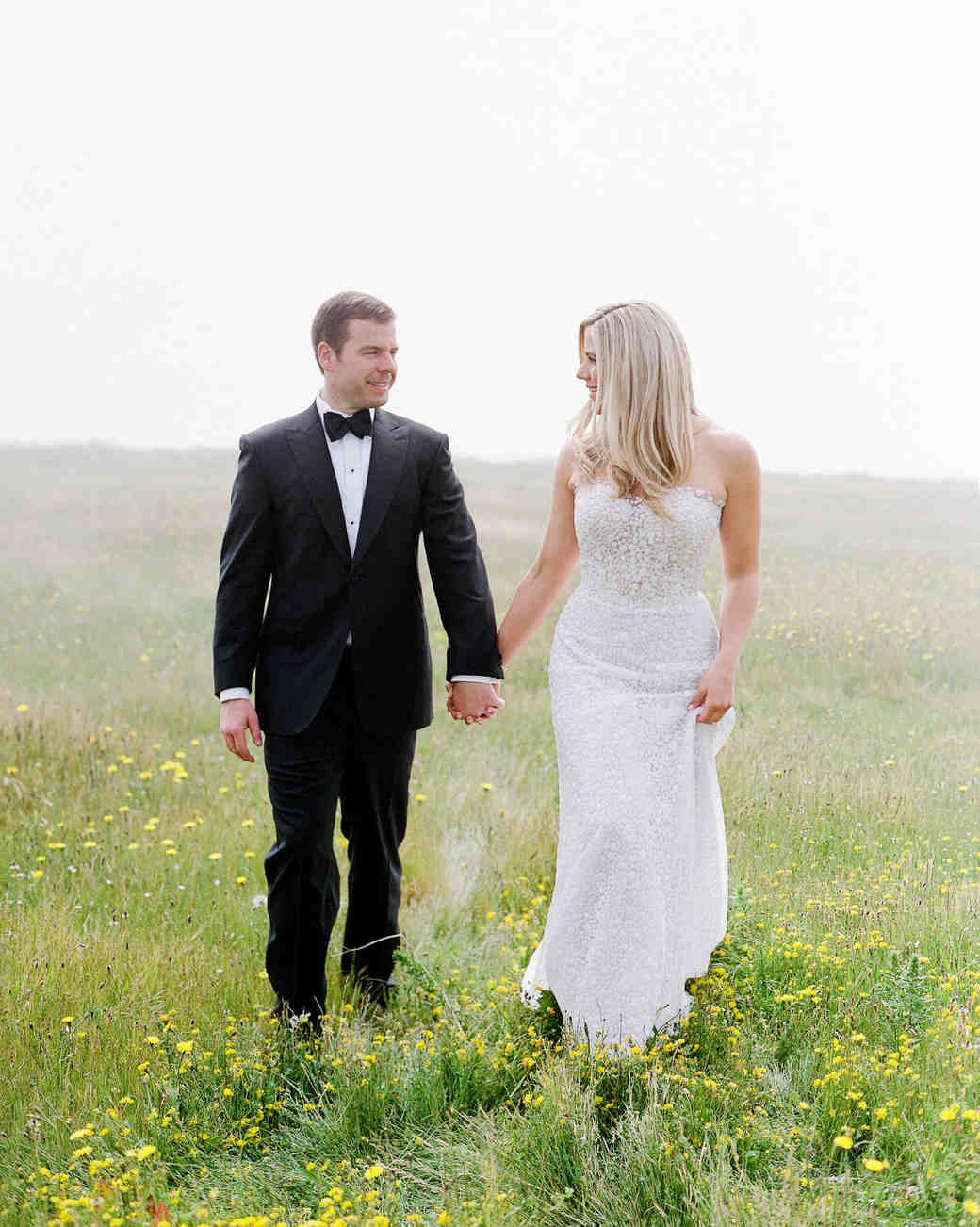 whitney zach wedding couple holding hands in field