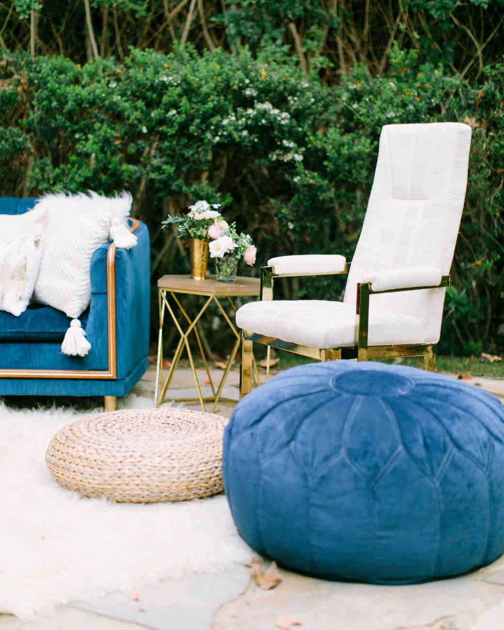 woven rattan wedding decor ottoman atop white fur rug at outdoor lounge area