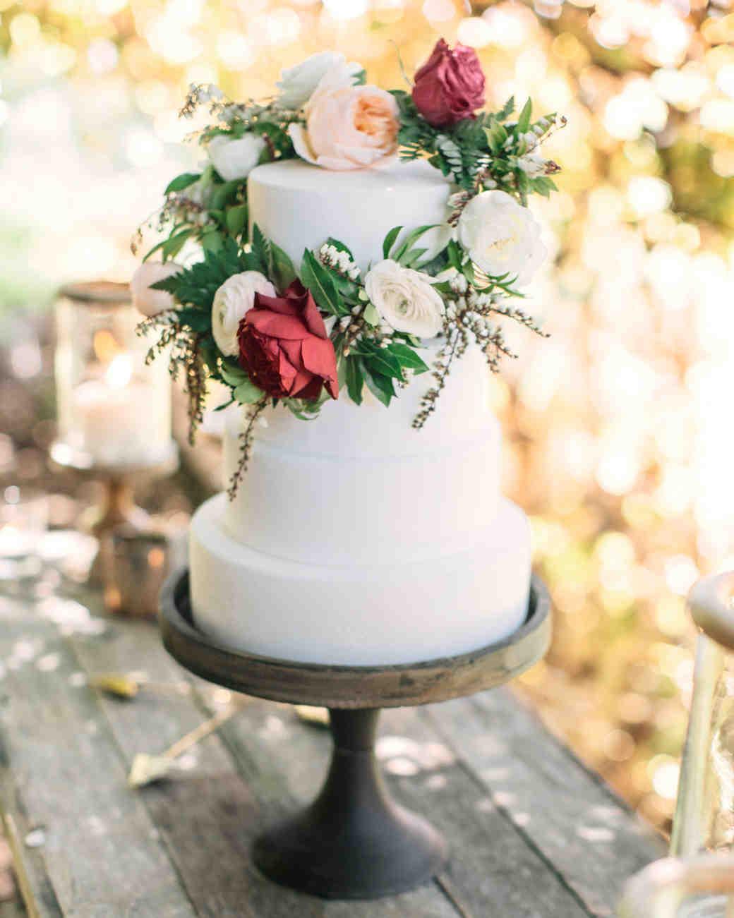 wedding wreath with roses decorating white wedding cake