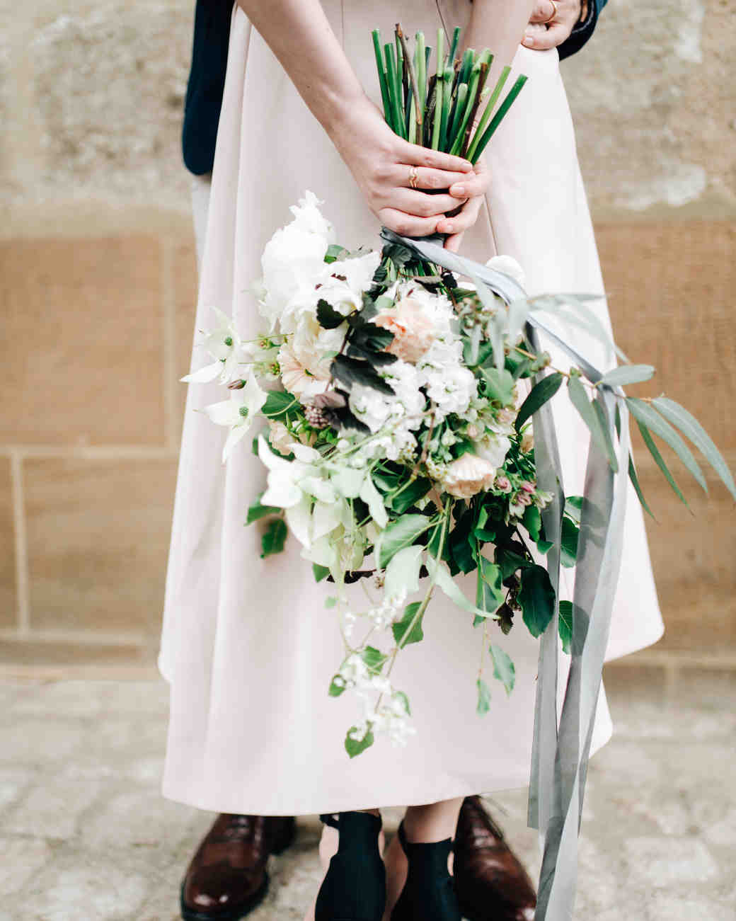 bride holding long-stemmed bouquet behind her back