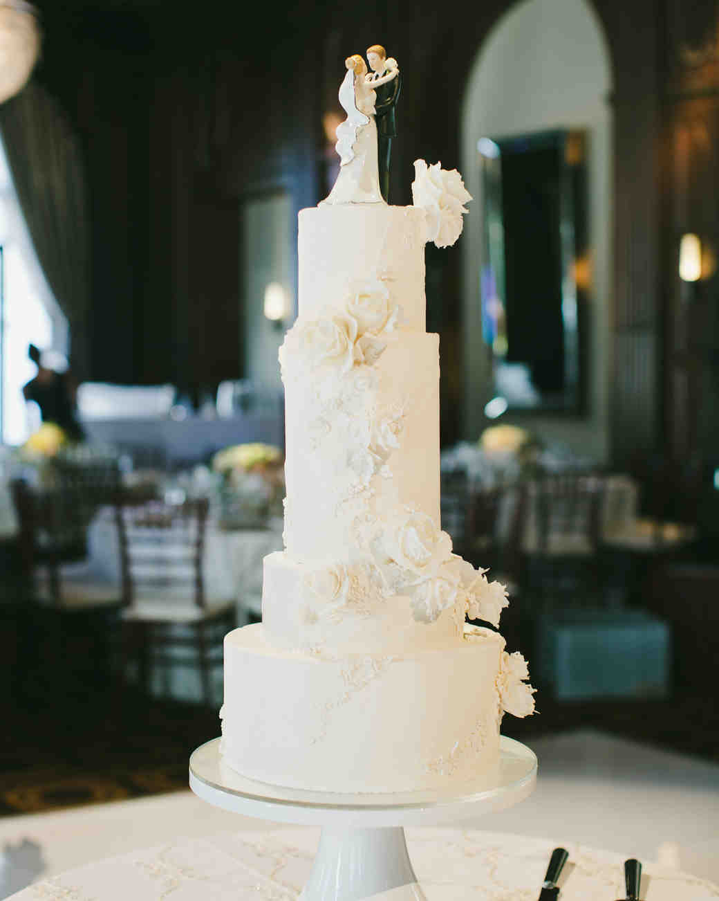 large white wedding cake with fondant flowers and topper