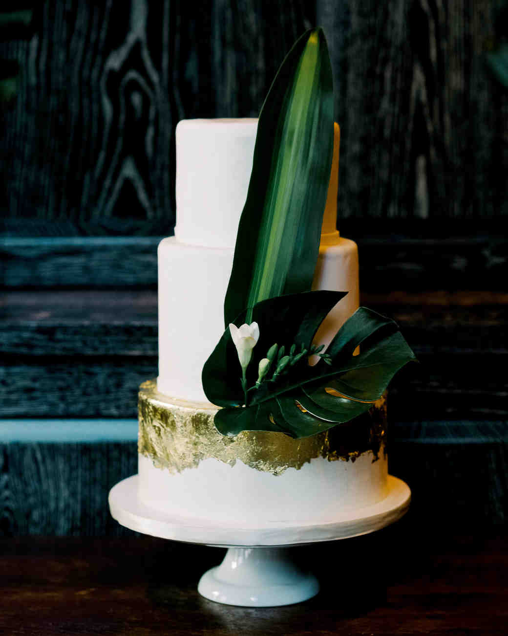 three tiered white wedding cake with gold sheet accents and a tropical leaf