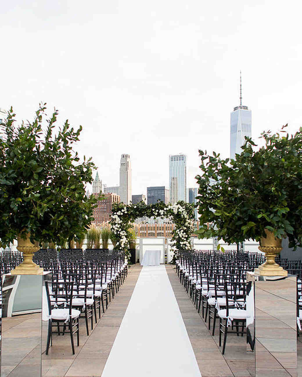 outdoor wedding aisle with white carpet over looking city