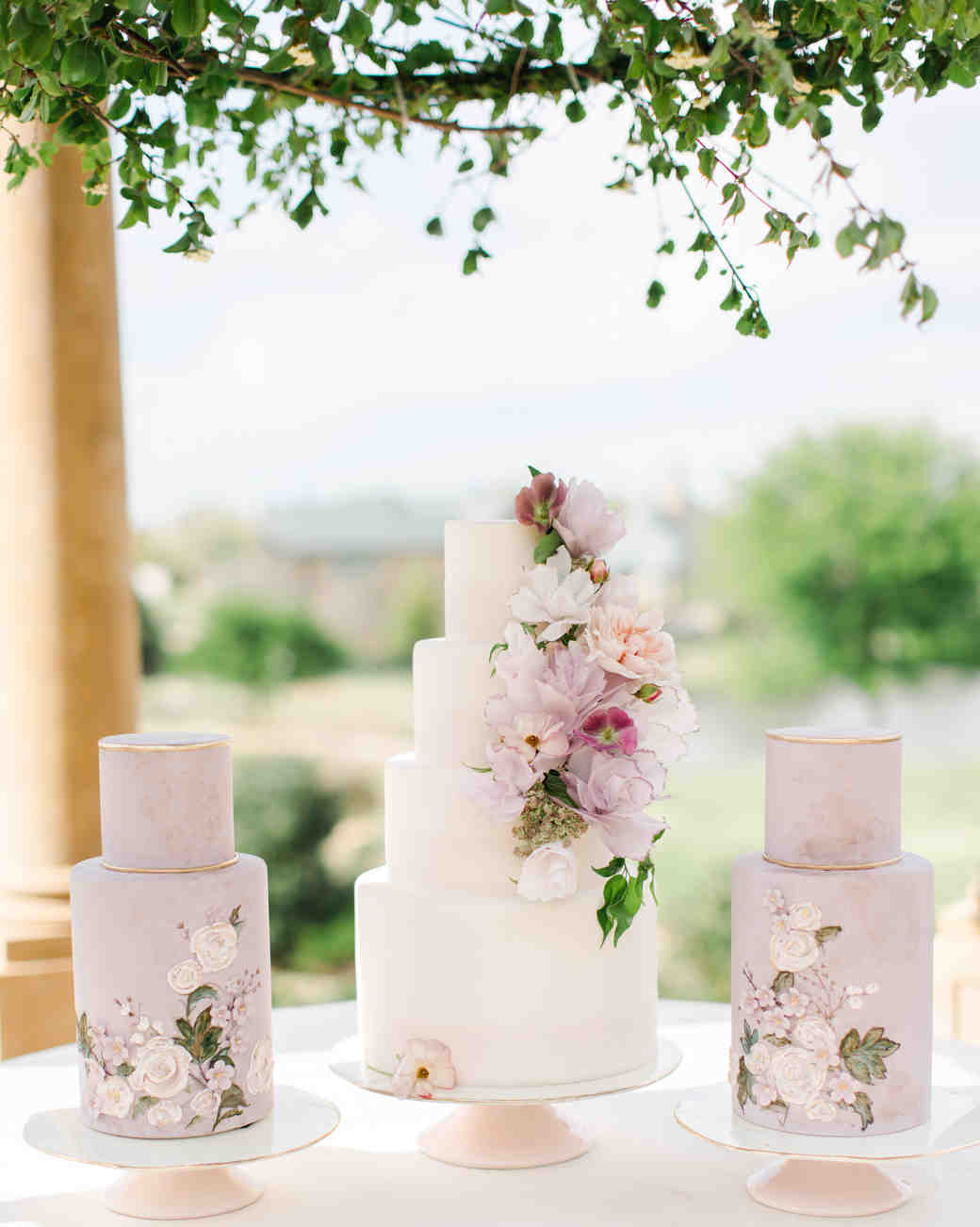 three lavender wedding cakes with flowers