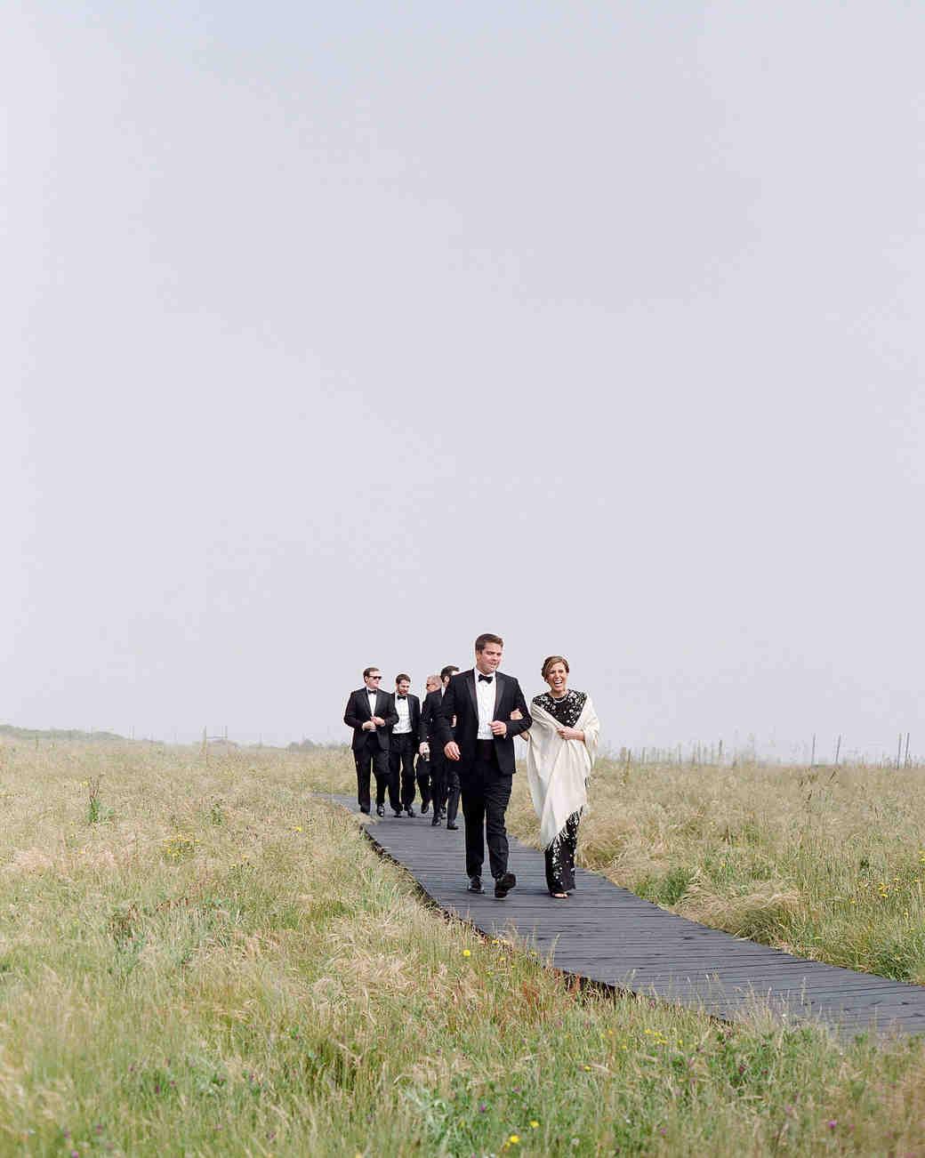 whitney zach wedding guests walking down wooden path in field