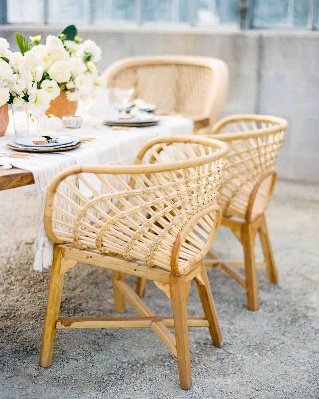 woven rattan wedding decor chairs around table decorated with white roses