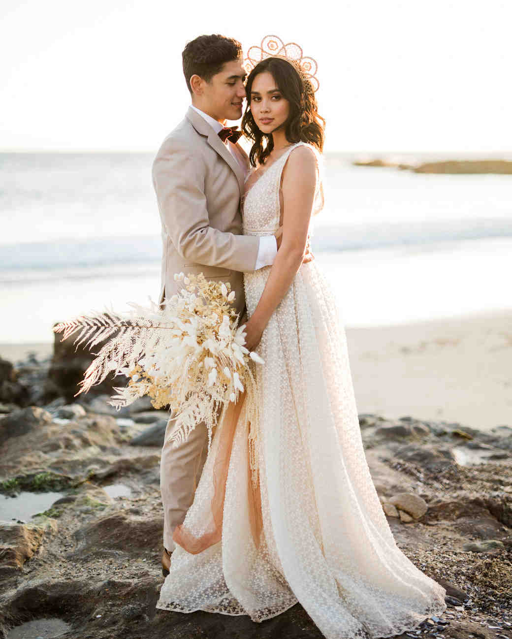 couple on beach with bride wearing rattan crown