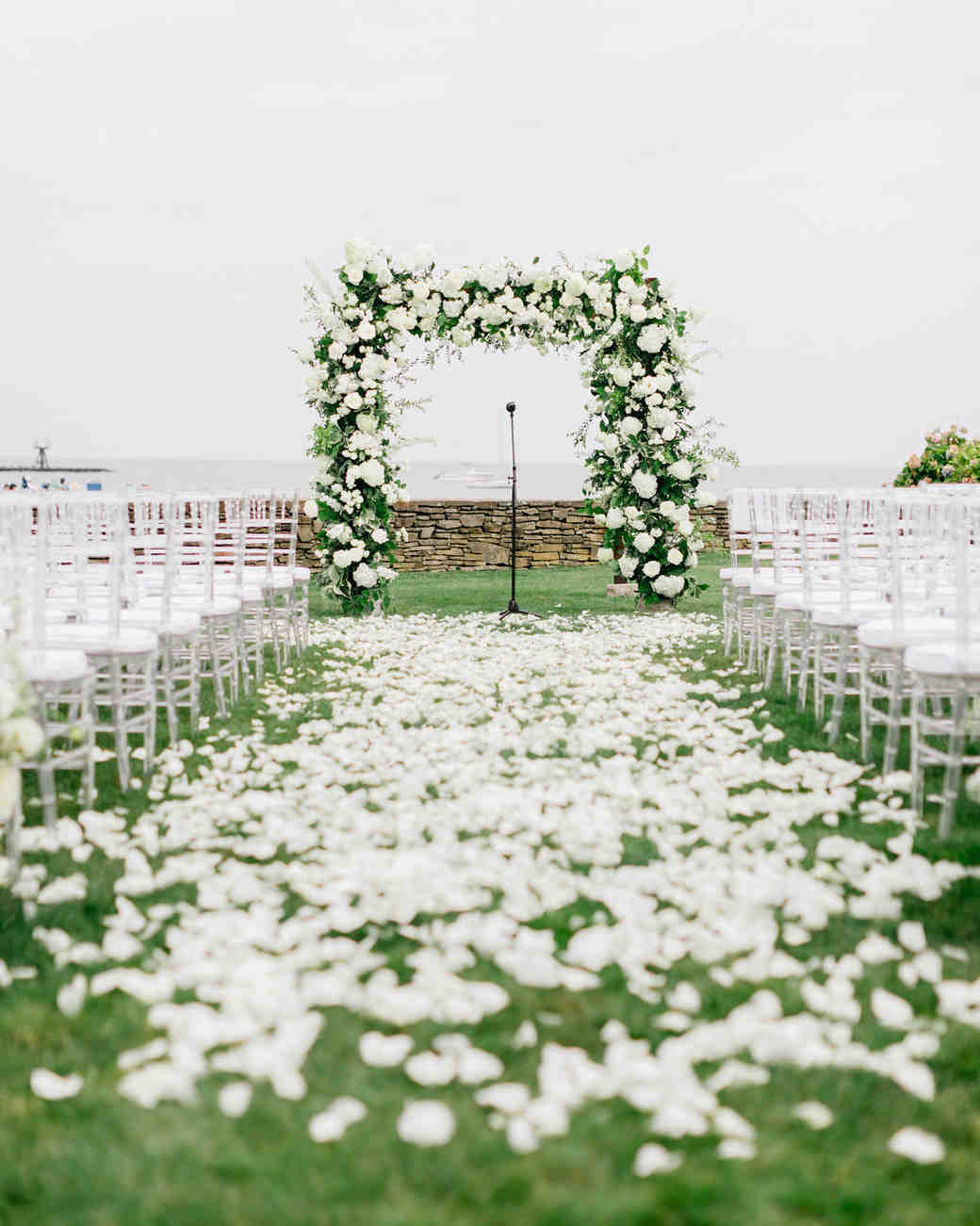 wedding ceremony setup white floral arch and aisle with flower petals