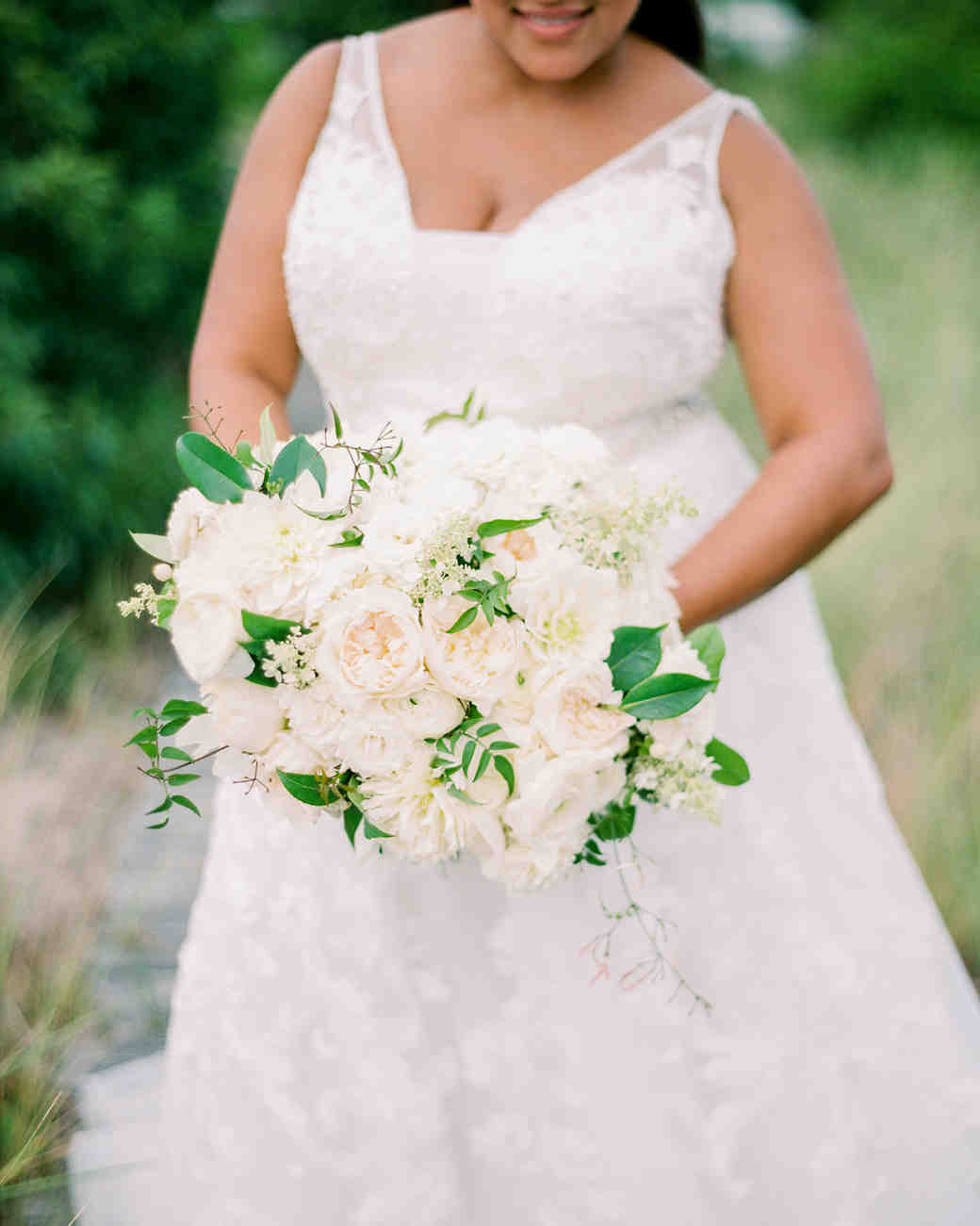 bride holding bouquet of white peonies