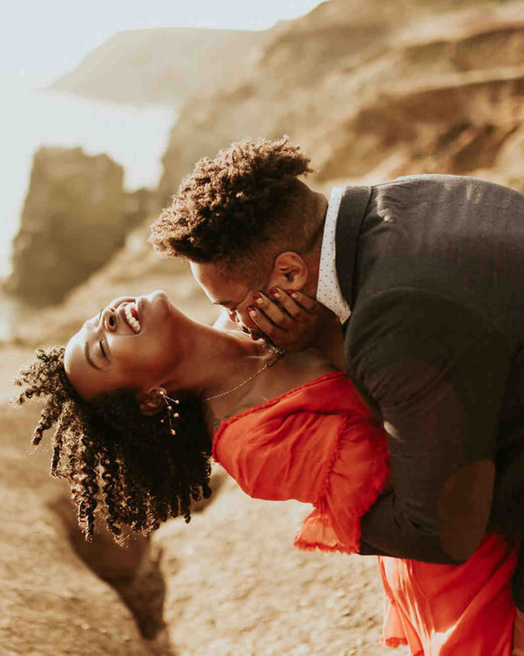 couple on beachside cliff engagement photo
