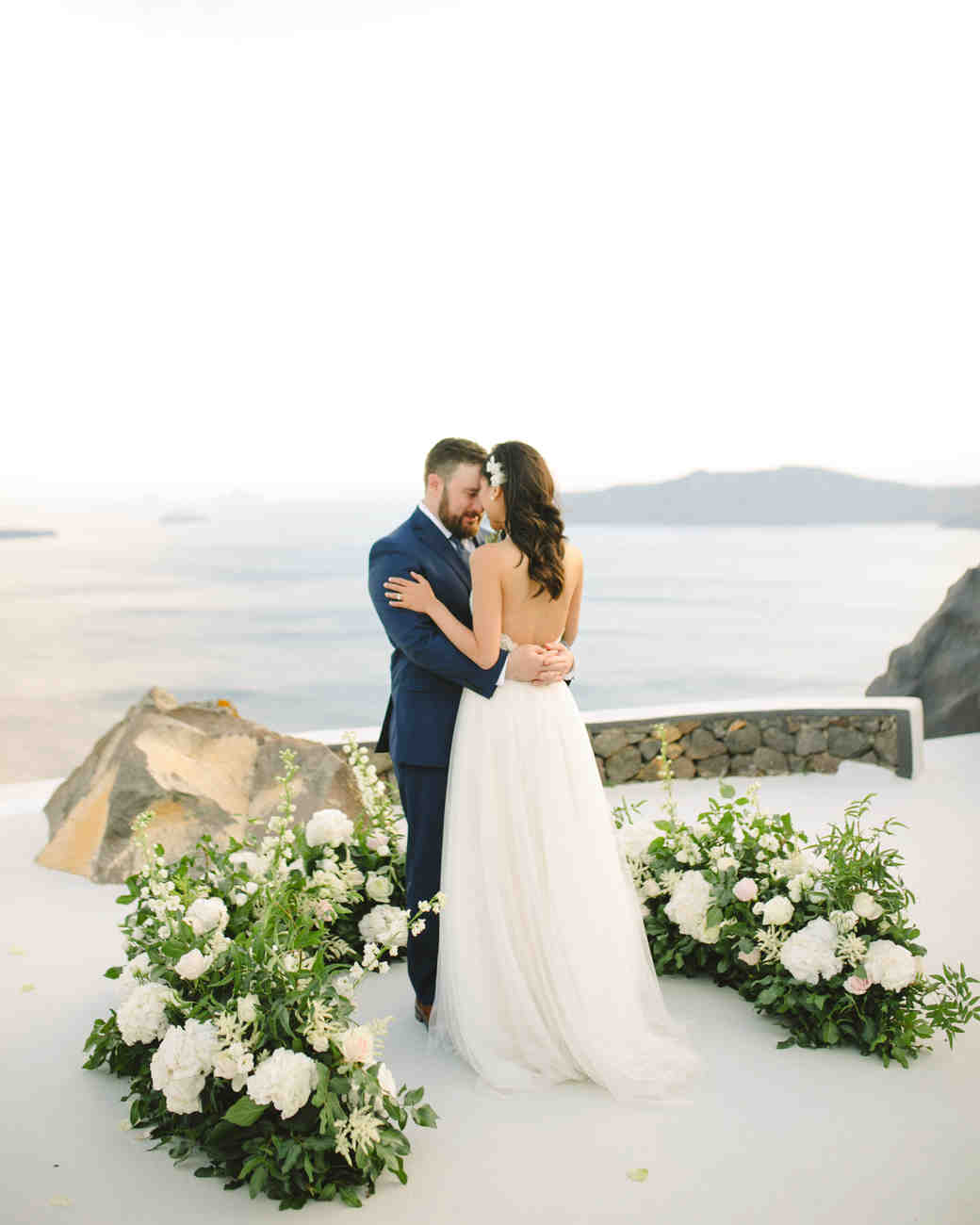 wedding ground floral arch greenery and white florals white flooring