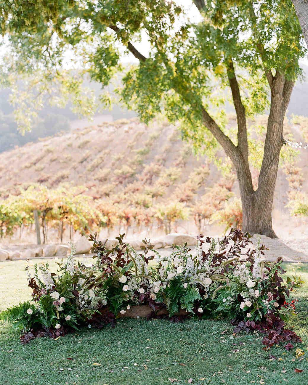 wedding ground floral arch dark hued blooms