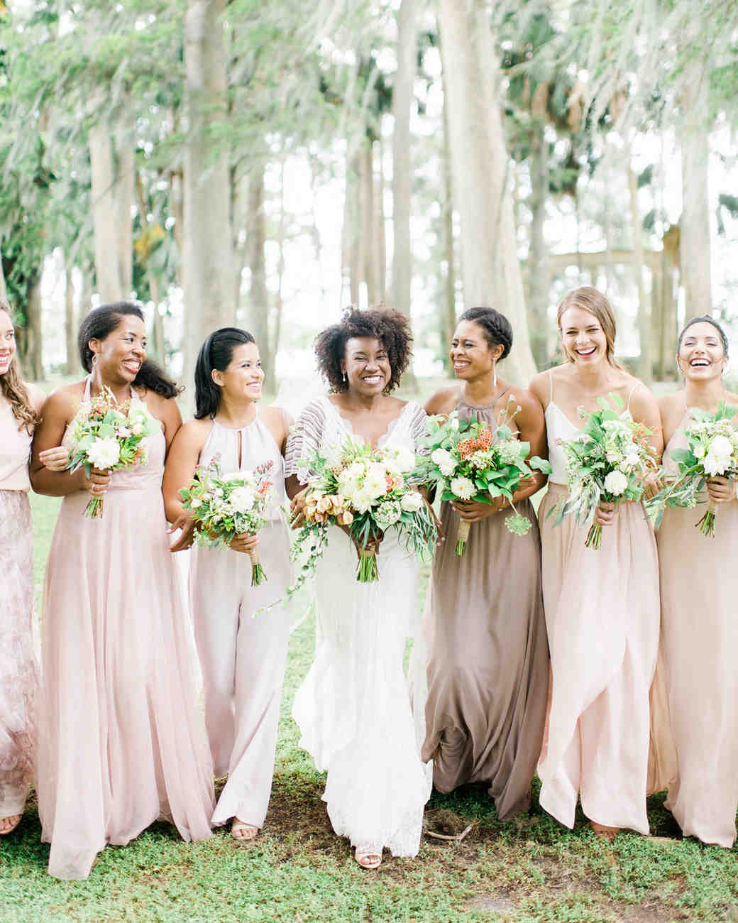 bridal party posing in front of trees featuring maid of honor wearing jumpsuit