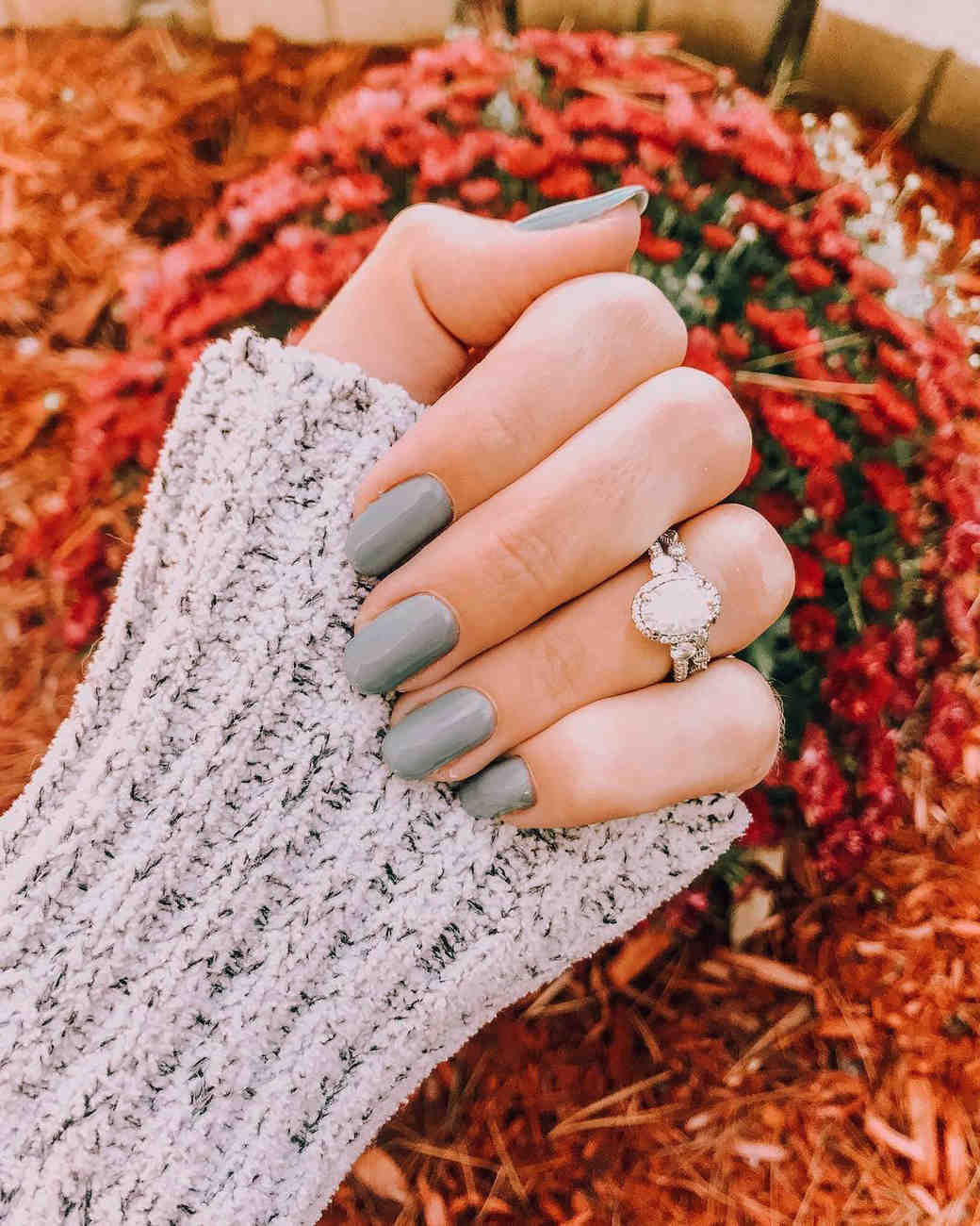 engagement ring selfie red floral backdrop and gray sweater