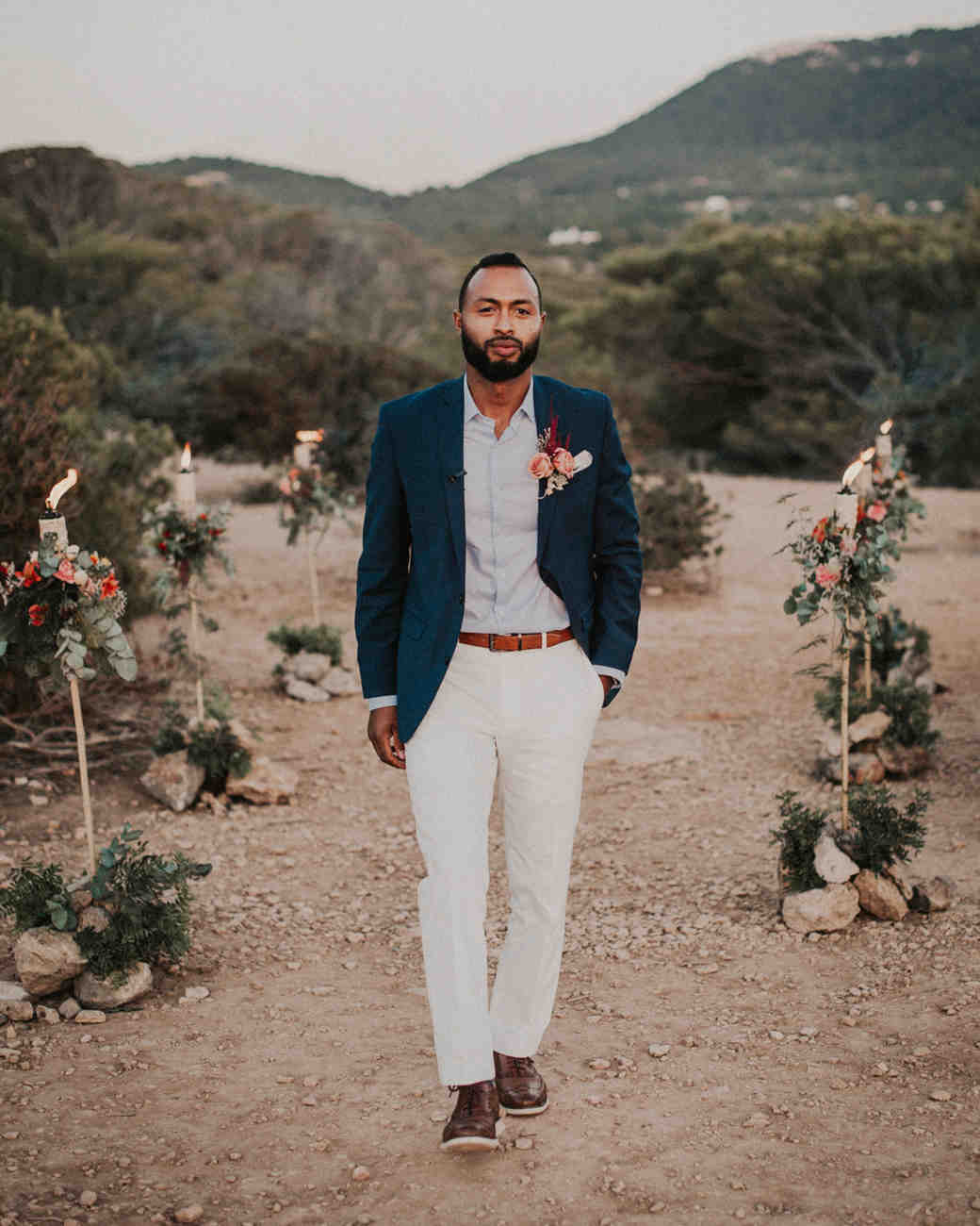 groom stands in front of floral lined isle