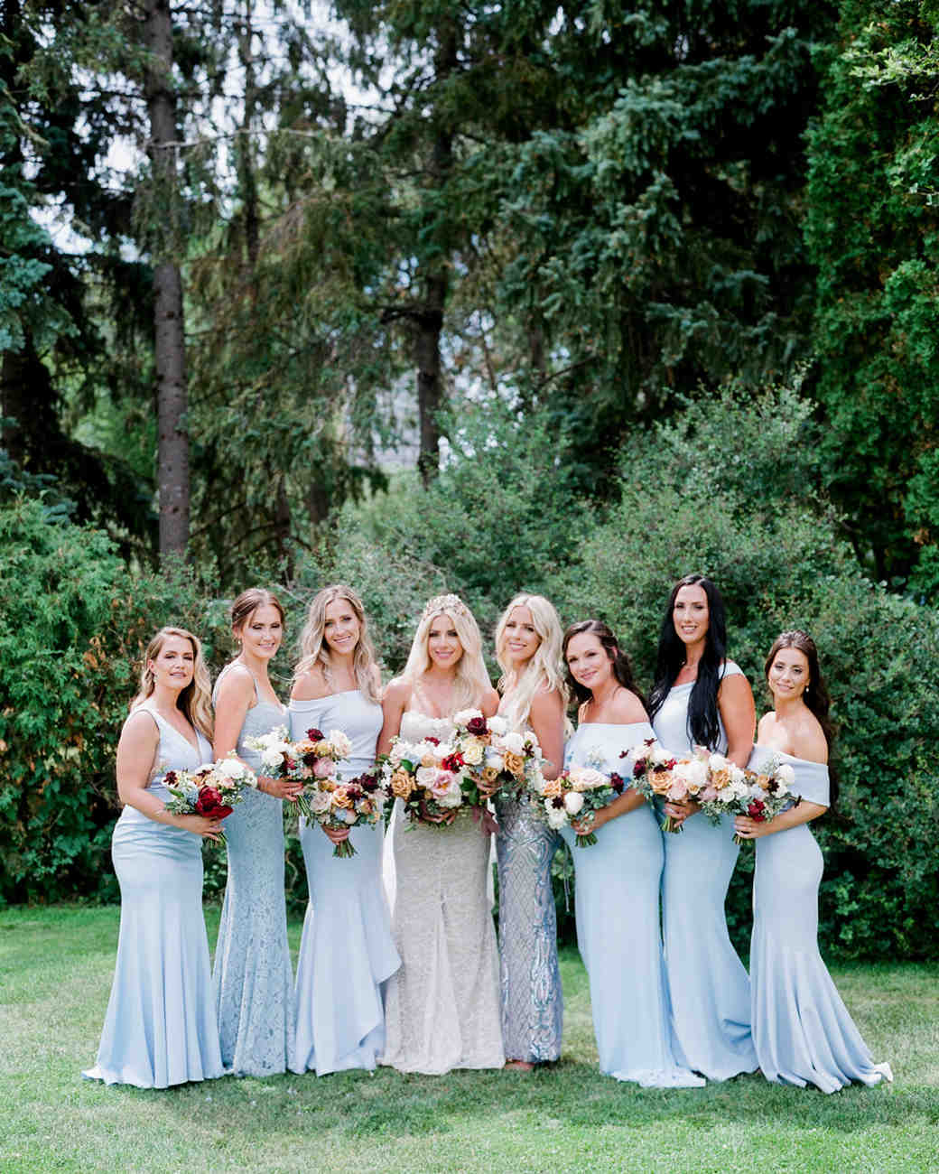 bride with bridesmaids wearing mismatched light blue gowns