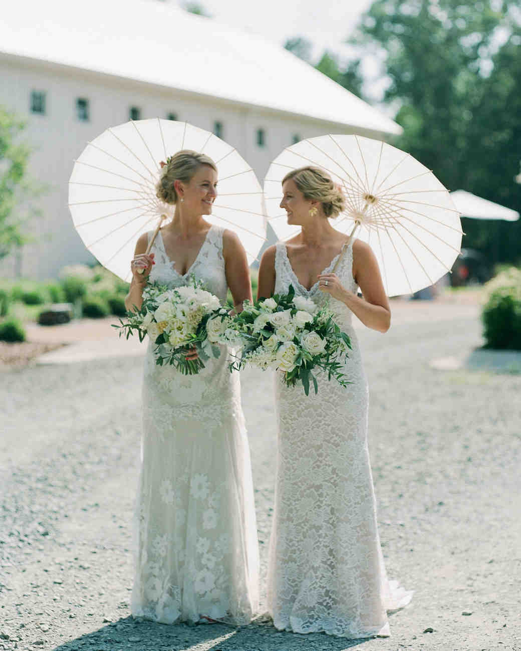 paige and kristine wedding brides holding parasols