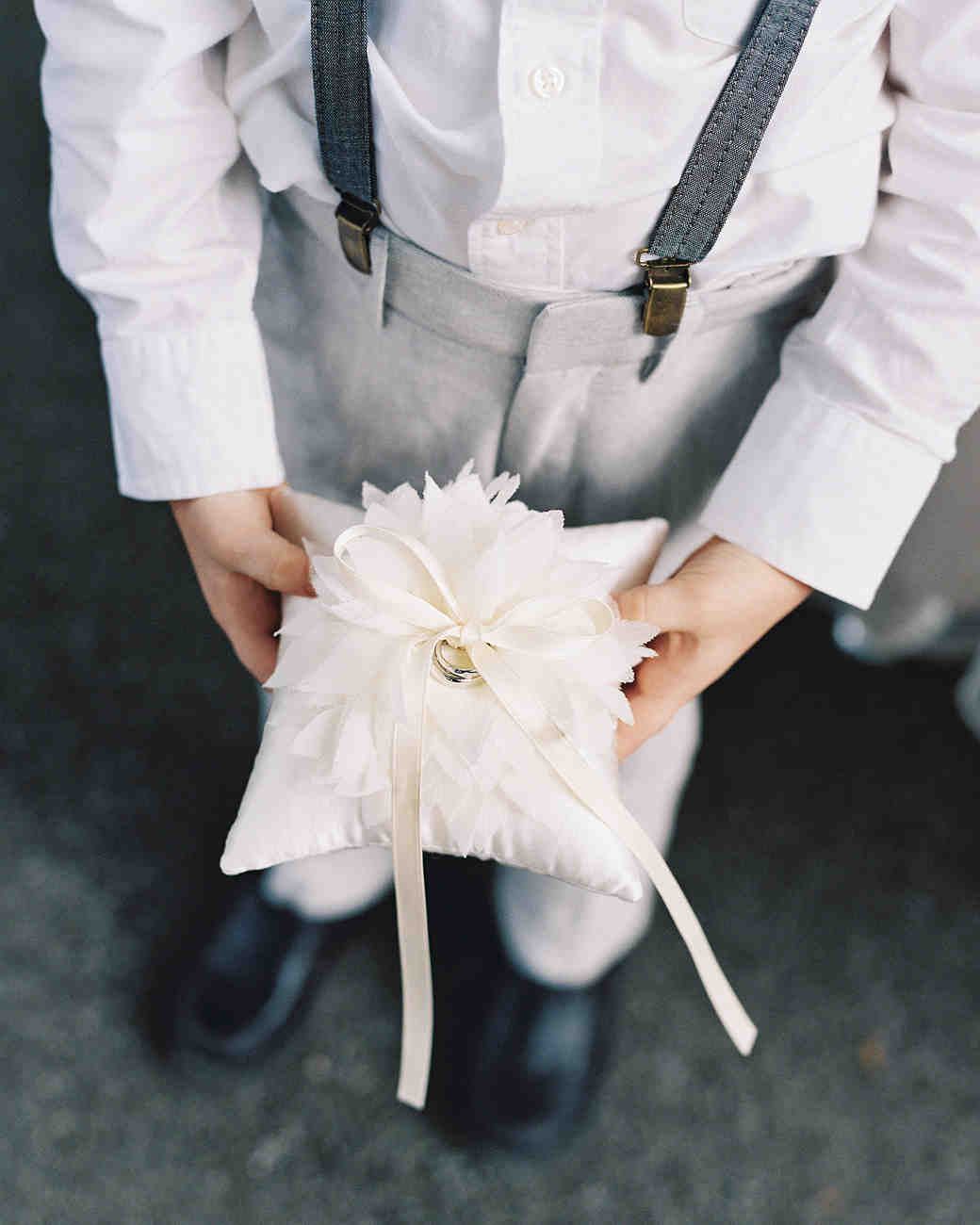 ring bearer holding pillow with large white flower