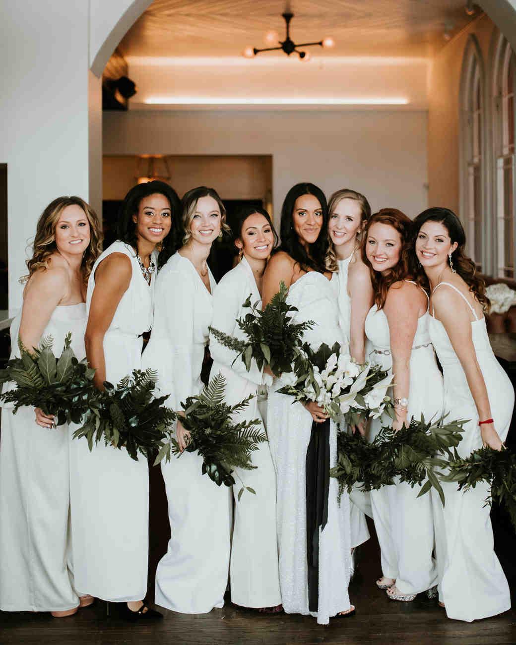 women wearing white bridesmaids jumpsuits holding greenery bouqets