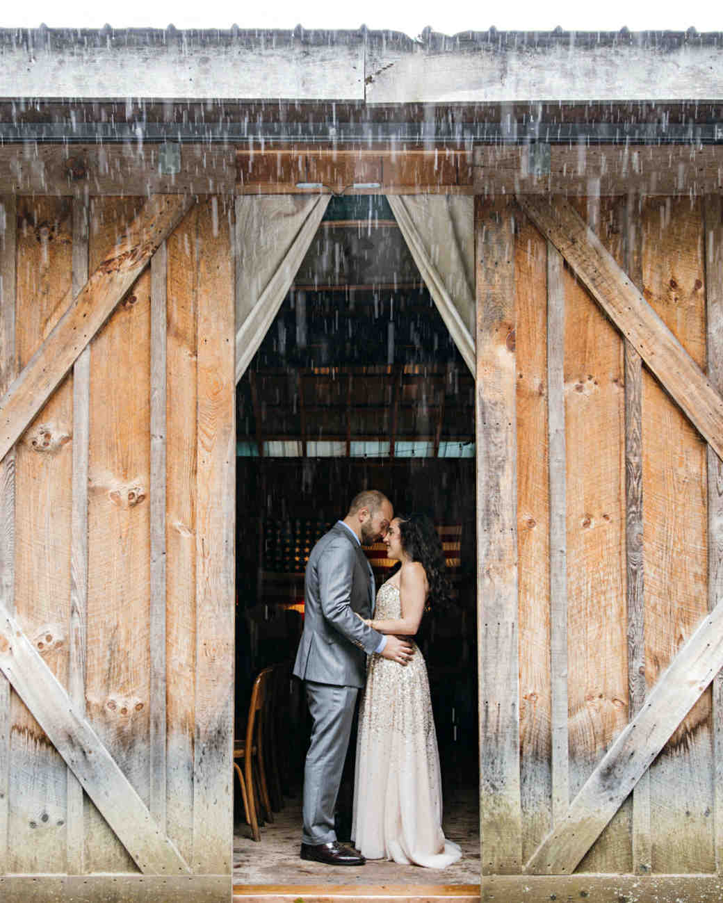 rainy wedding couple in barn