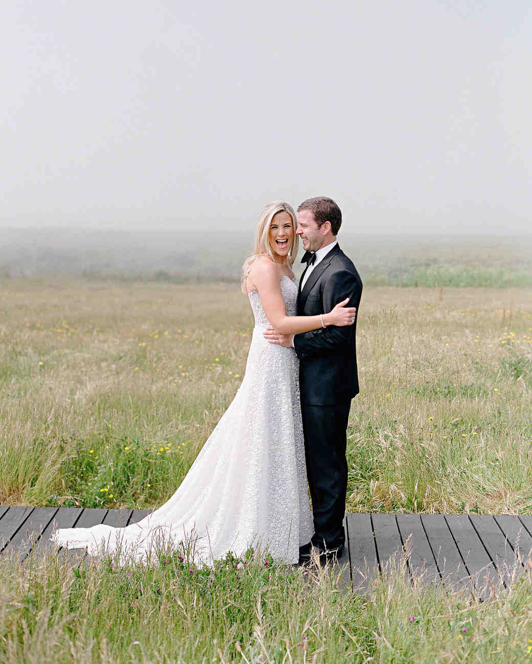 whitney zach wedding couple embracing in field bride laughing