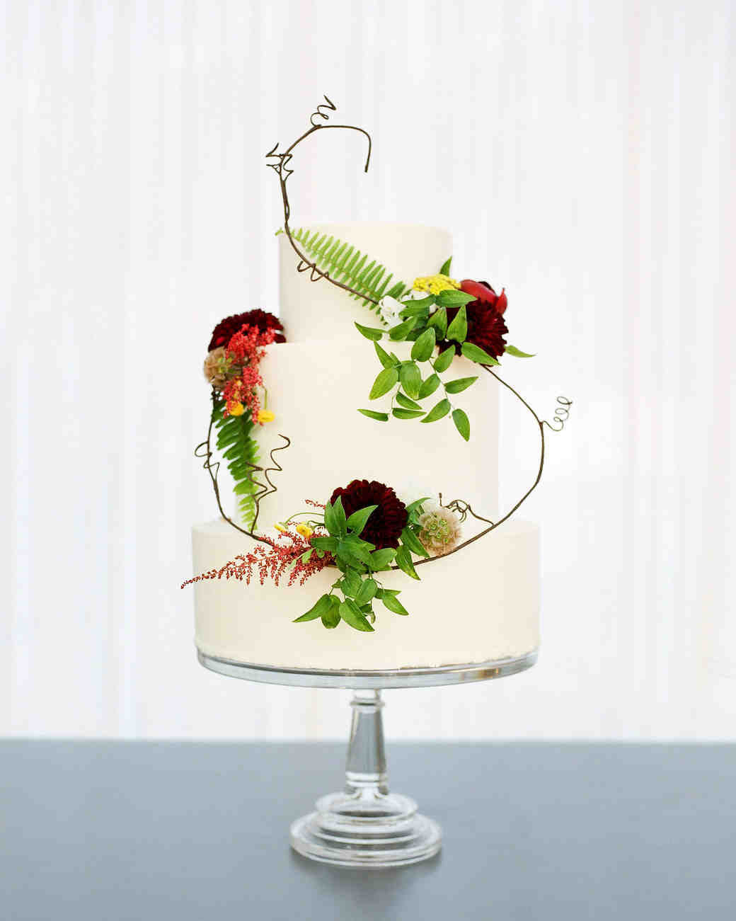 Three Tiered Wedding Cake with Ferns and Burgundy and Orange Flowers