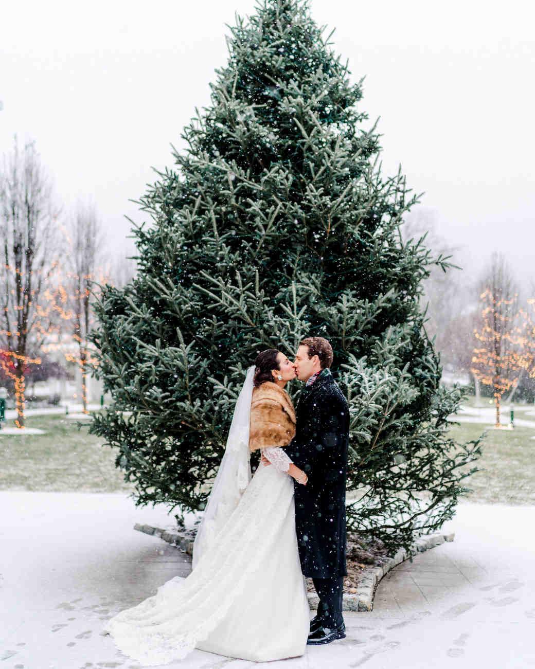 lauren christian christmas wedding couple outside kissing evergreen tree snowing