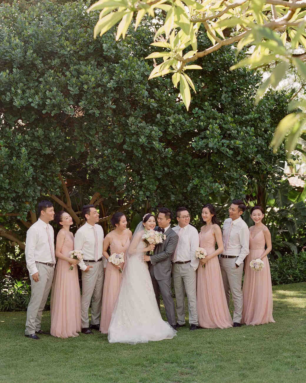 hawaiian wedding party pose in front of tree line