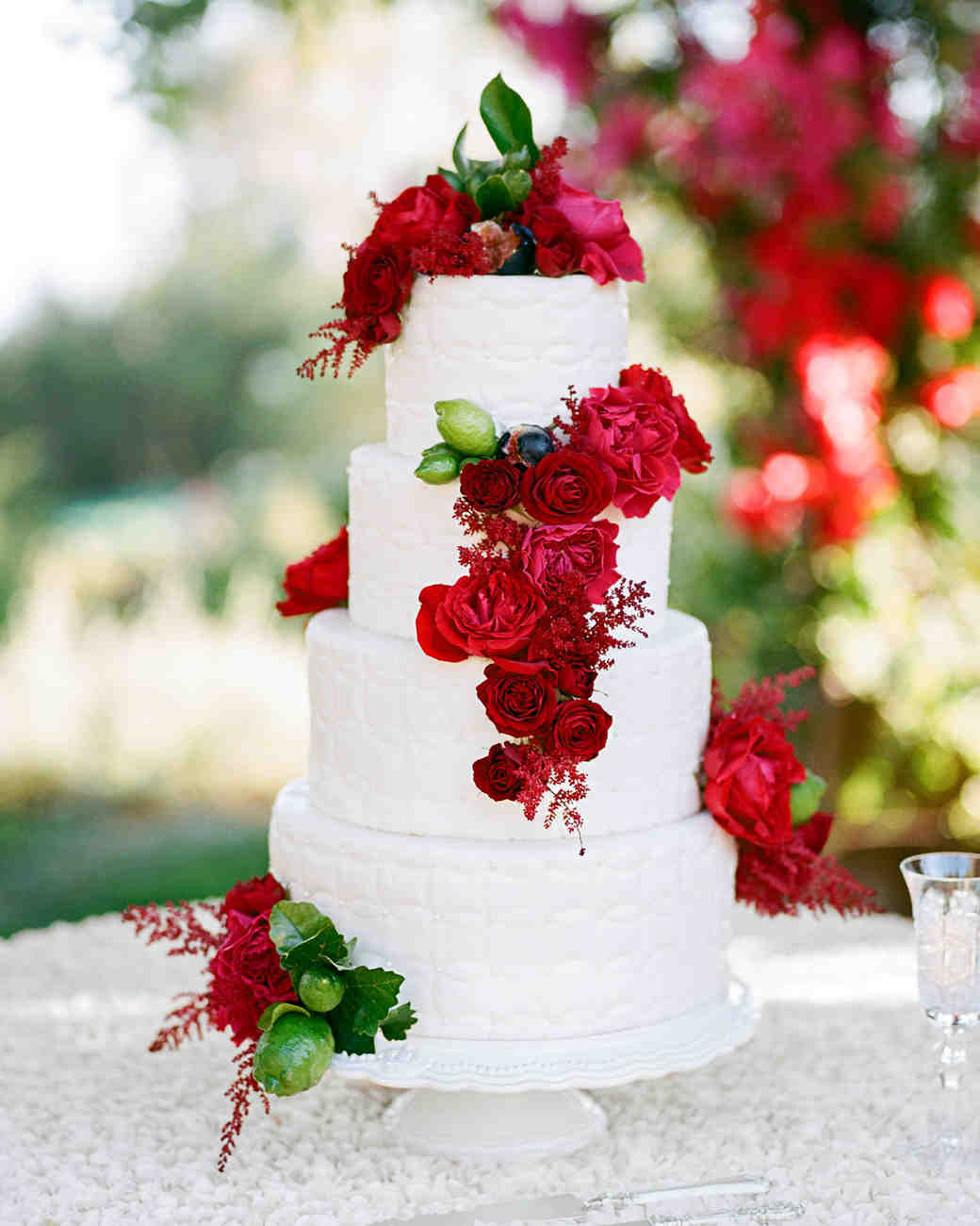 White Wedding Cake with Bright Crimson Flowers and Green Limes