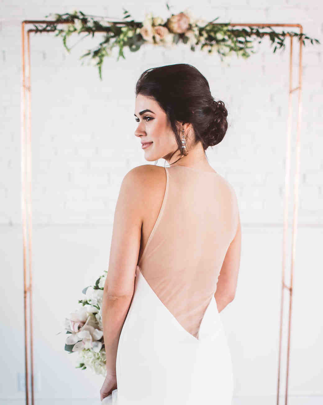 rose gold wedding ideas bride beneath metallic arch