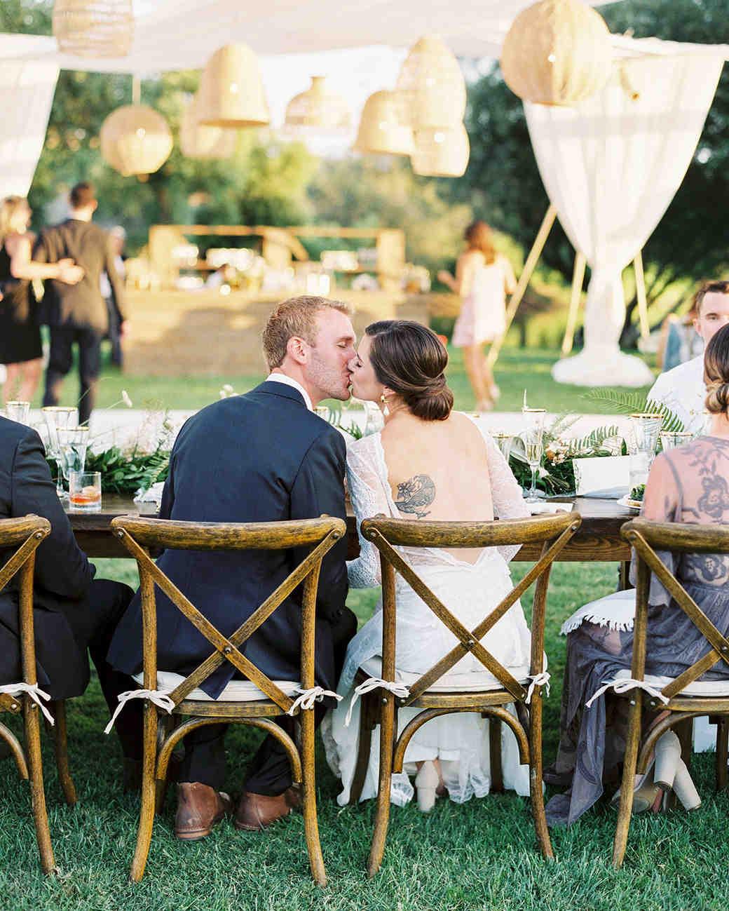 jena donny wedding couple kiss sitting at reception