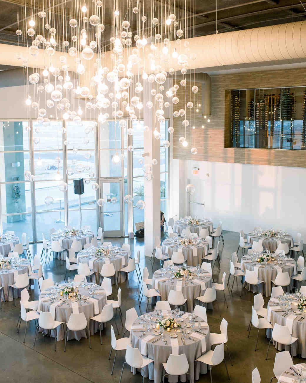 wedding reception round tables below hanging lights globes