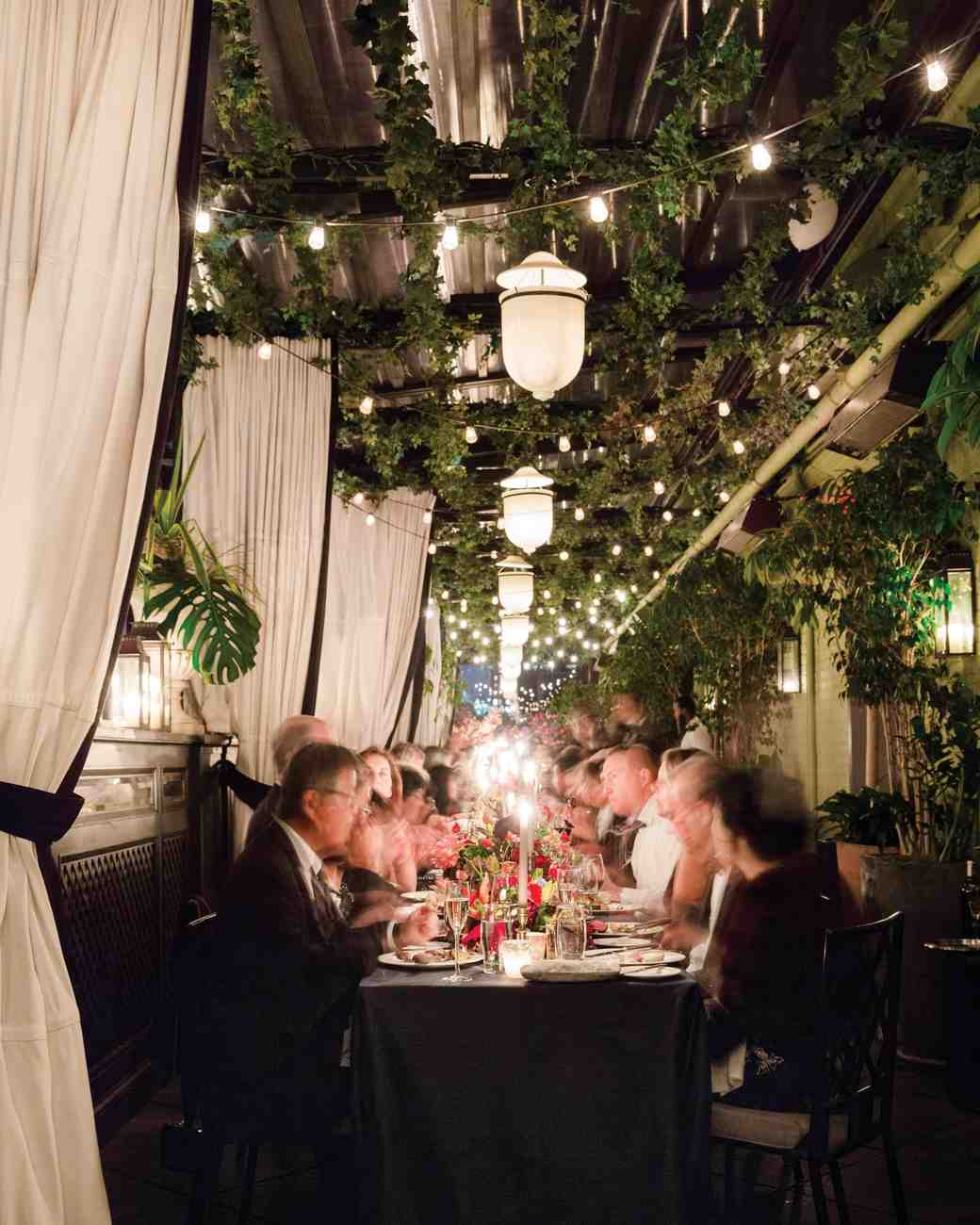 Hanging Lanterns and Greenery Garlands Over Reception Tables