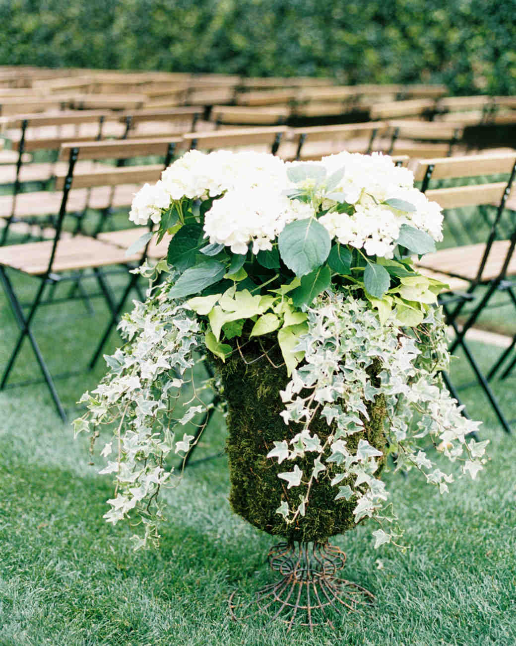 large floral ceremony arrangements of greenery and a white flower