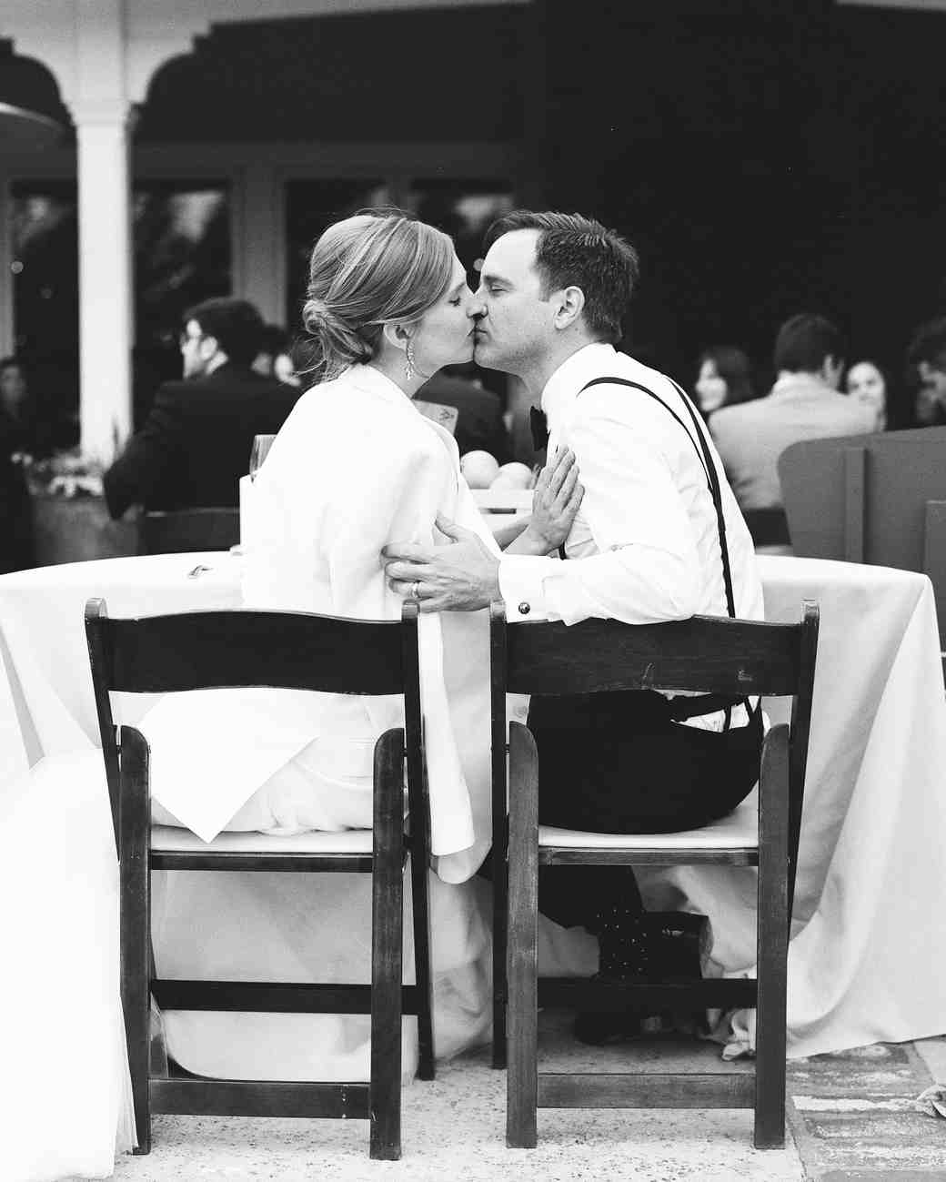 couple kissing at table
