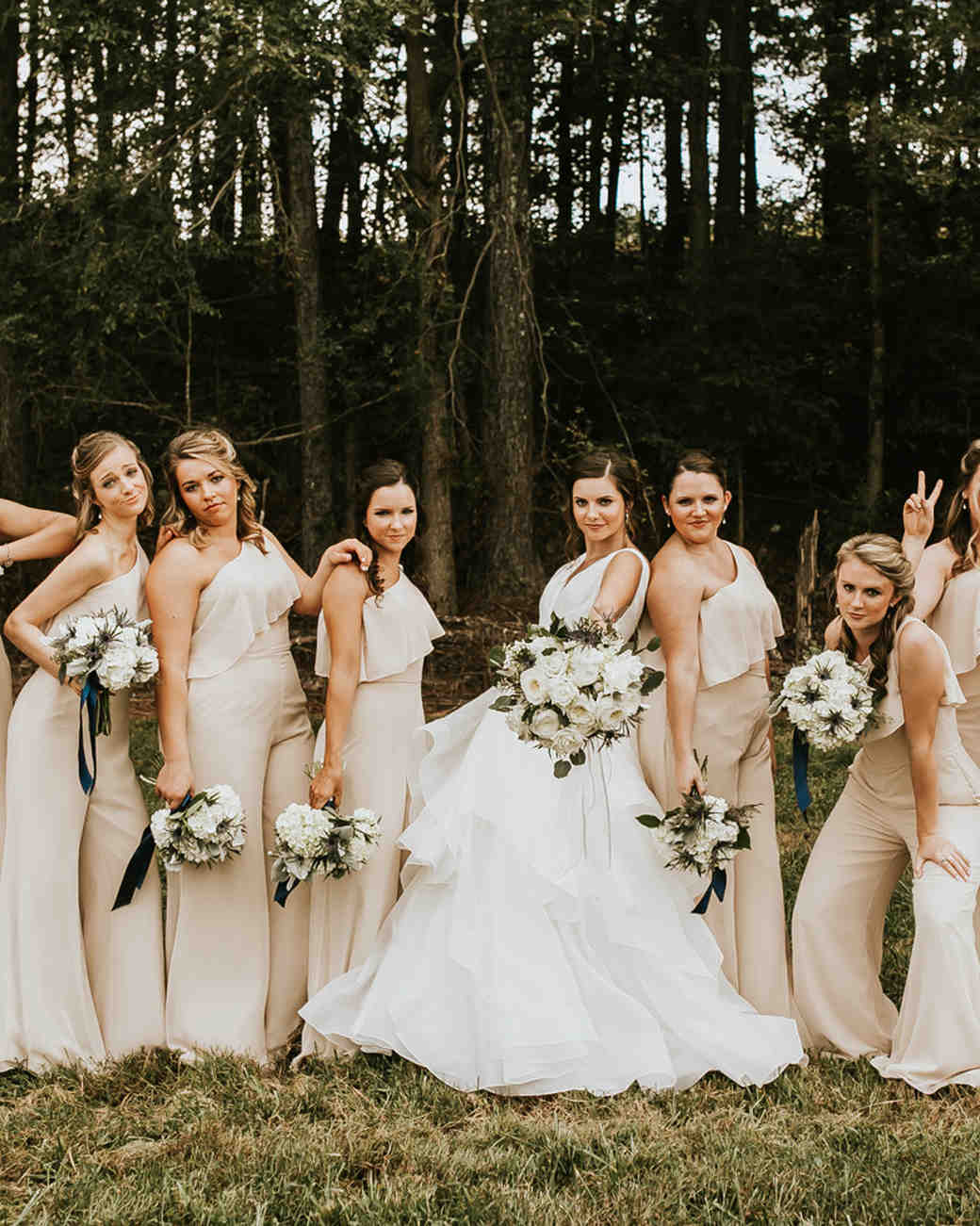 wedding party standing in front of forest with women wearing bridesmaids jumpsuits