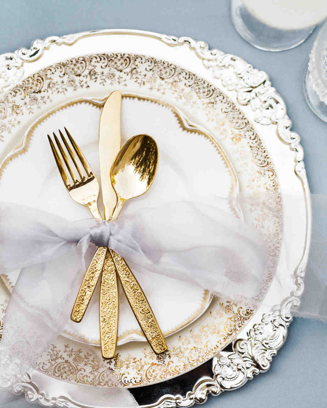 metallic wedding cuttlery and plates in place setting