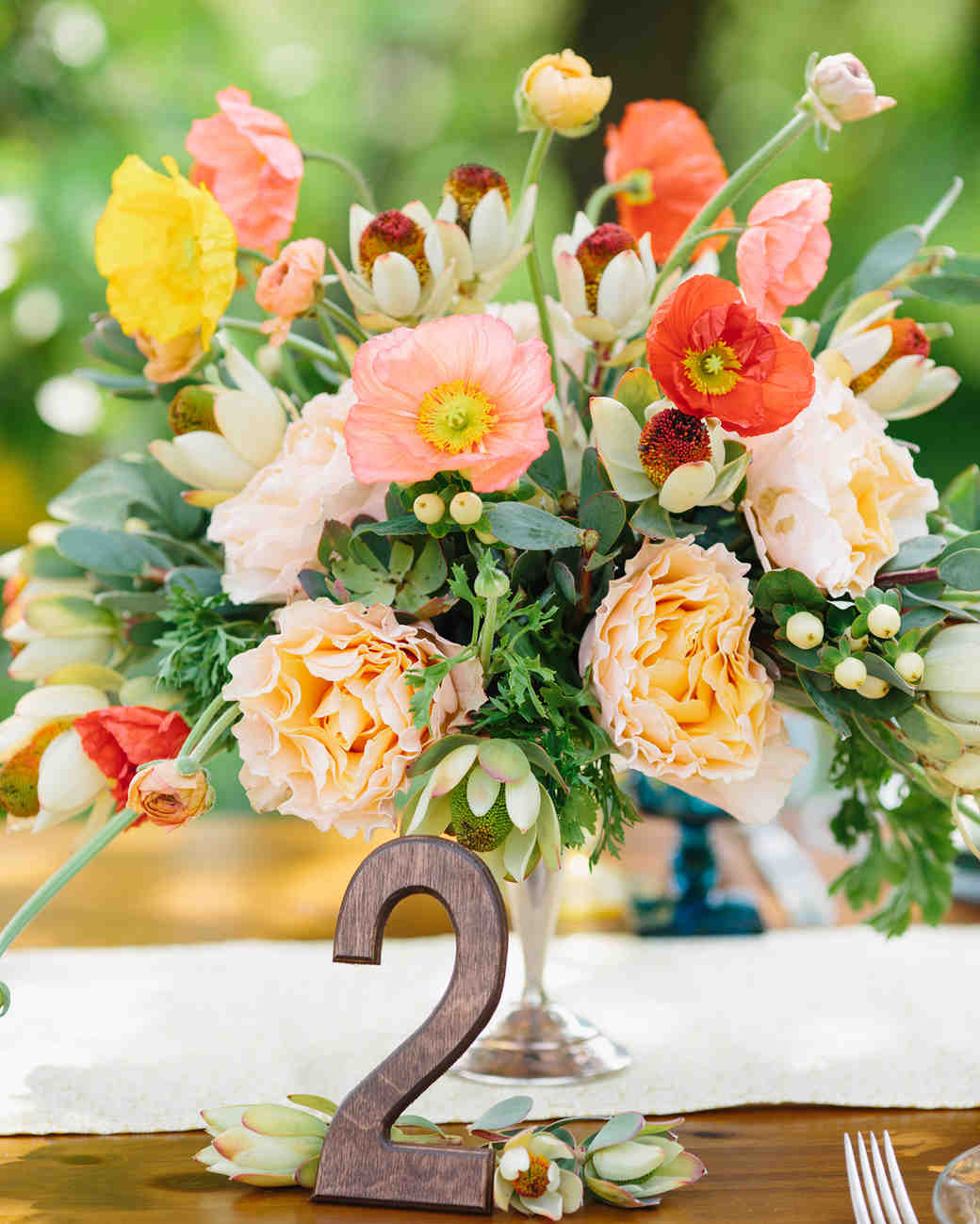 Colorful summer wedding centerpiece with poppies and roses