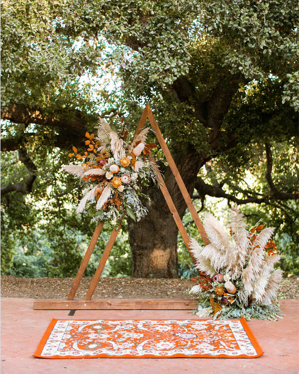wedding later decorated with orange florals and pampas grass
