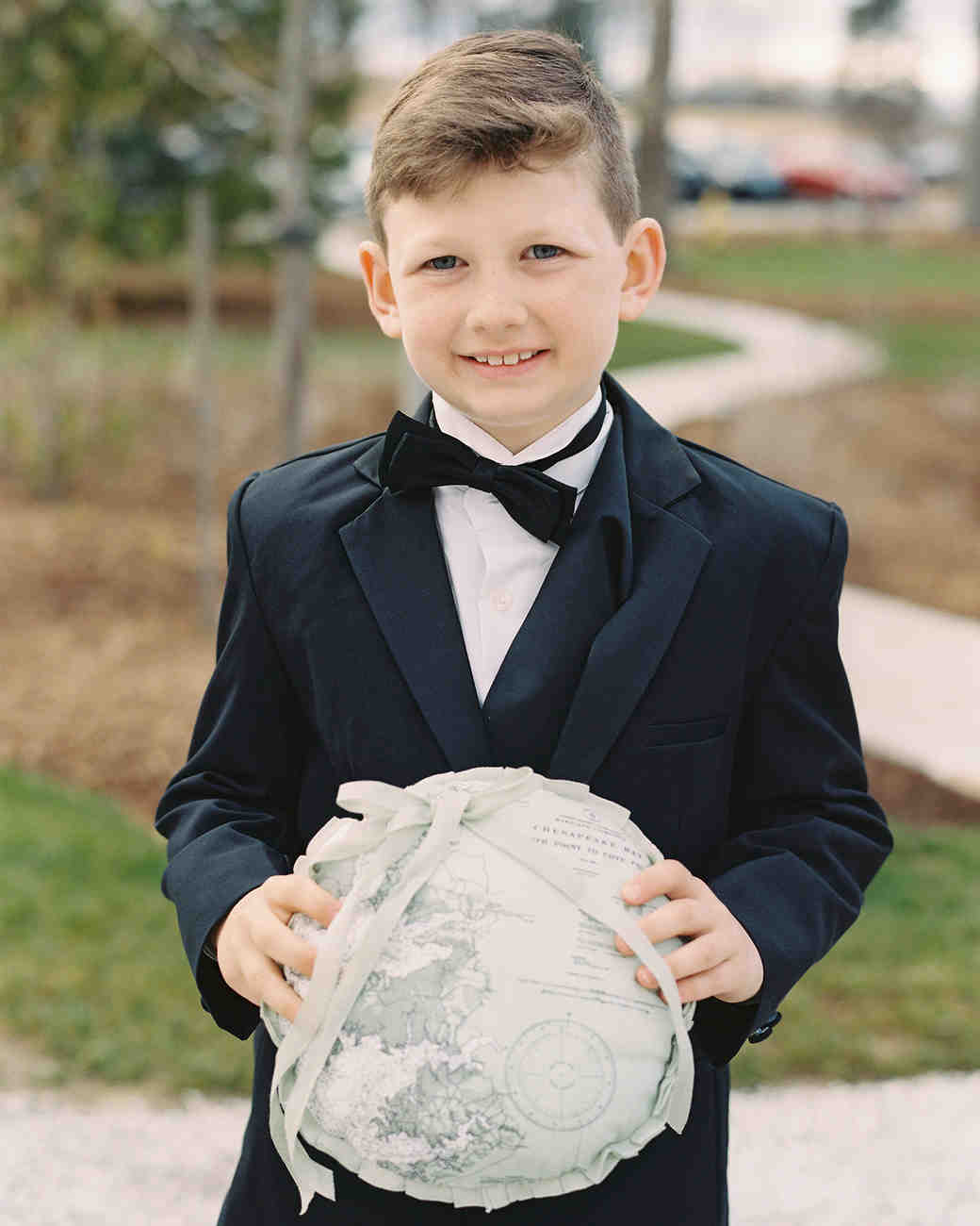 ring bearer holding map pattern pillow at wedding