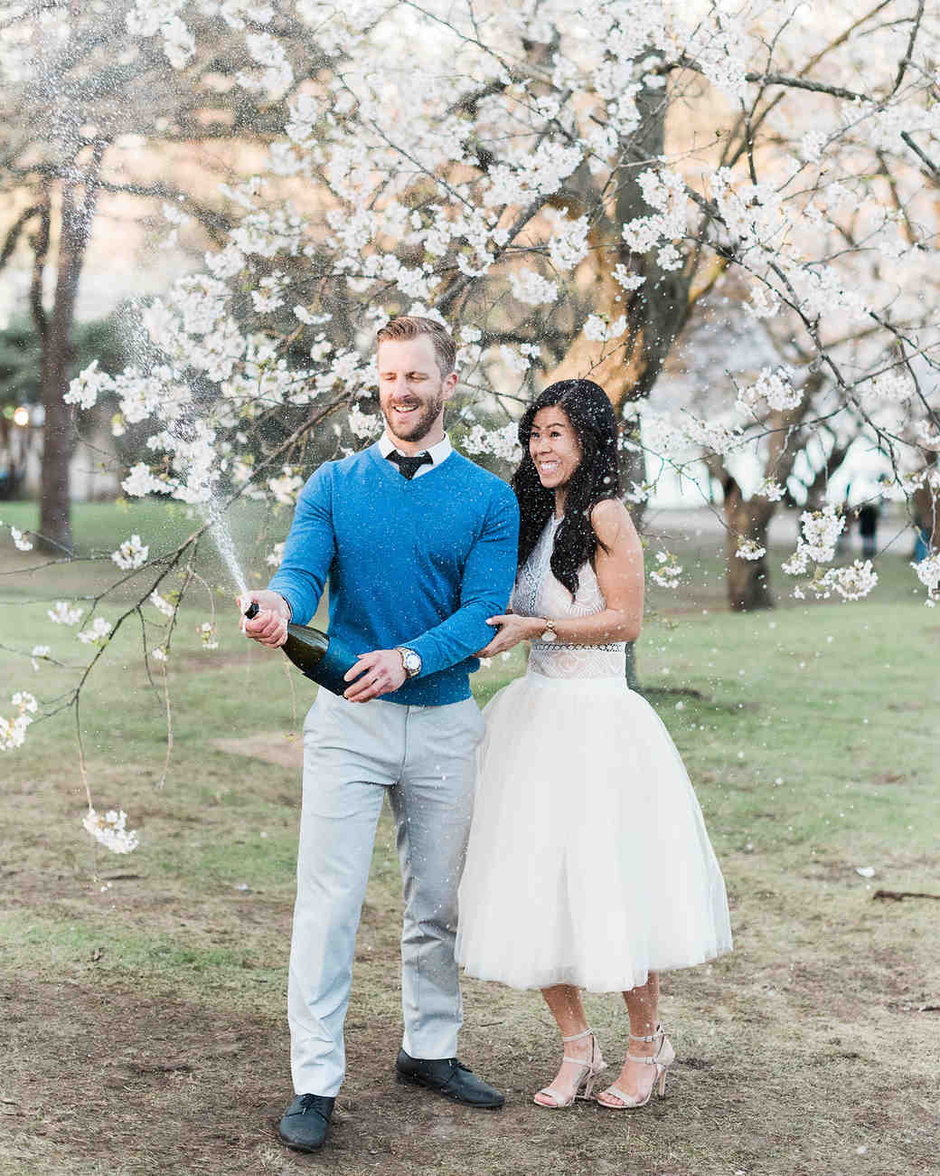couple popping champagne engagement photo